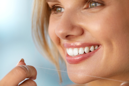 flossing: Dental Health. Closeup Portrait Of Beautiful Happy Smiling Young Woman With Perfect Smile Cleaning Healthy White Teeth, Flossing Using Floss. Tooth Care, Oral Hygiene Concept. High Resolution Image