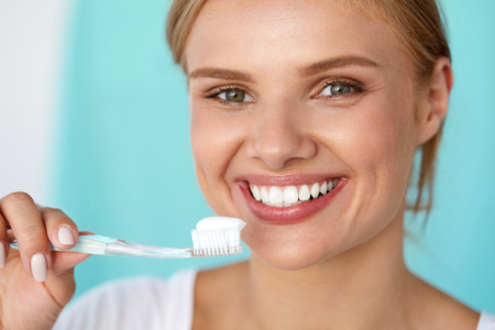 Healthy White Teeth. Closeup Portrait Of Beautiful Happy Smiling Woman With Fresh Perfect Smile Brushing Teeth Using Toothbrush With Toothpaste. Dental Health Care Concept. High Resolution Image