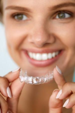 White Smile. Portrait de belle femme souriante avec des dents blanches droites holding de blanchiment des dents Plateau, Fille Utilisation dentaire Whitener. Dental Beauty Concept traitement. Image à haute résolution