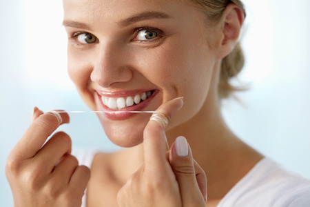 Dental Care. Closeup Portrait Of Beautiful Happy Smiling Young Woman With Perfect Smile Cleaning, Flossing Healthy White Teeth Using Floss. Mouth Hygiene, Oral Health Concept. High Resolution Image