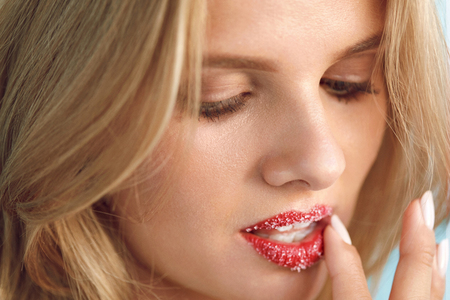 full lips: Lip Skin Care. Closeup Of Beautiful Young Woman With Fresh Beauty Face, Soft Pure Skin And Sweet Plump Full Lips Touching Cosmetic Sugar Lip Scrub On Her Lips. Cosmetics Concept. High Resolution Image Stock Photo