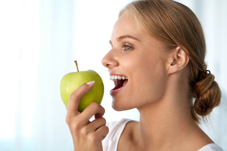 dental health: Healthy Nutrition. Closeup Portrait Of Beautiful Smiling Woman With Perfect Smile, White Teeth And Fresh Face Eating Organic Green Apple. Dental Health, Diet Food Concepts. High Resolution Image Stock Photo