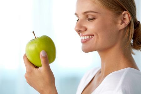 Zdravá výživa. Closeup portrét krásné usmívající se ženy s dokonalým úsměvem, bílé zuby a čerstvé tvář jíst organické zelené jablko. Zubní zdraví, koncepty stravy. Obrázek s vysokým rozlišením
