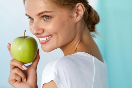 Salud dental. Retrato de detalle de hermosa mujer sonriente feliz con sonrisa perfecta, dientes blancos sana y fresca de la cara sostiene la manzana verde. Comida sana, Conceptos alimentos de la dieta. Imagen de alta resolución