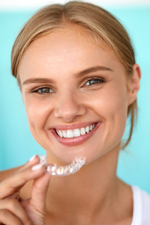 a tooth are beautiful: White Teeth. Closeup Portrait Of Beautiful Happy Woman With Perfect White Smile Using Teeth Whitening Tray. Smiling Girl Holding Medical Invisible Braces. Dental Health Concept. High Resolution Image
