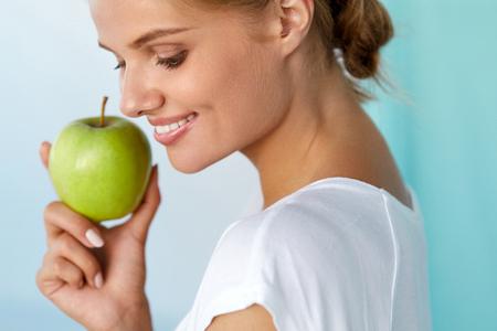 dientes sanos: Salud dental. Retrato de detalle de hermosa mujer sonriente feliz con sonrisa perfecta, dientes blancos sana y fresca de la cara sostiene la manzana verde. Comida sana, Conceptos alimentos de la dieta. Imagen de alta resolución Foto de archivo