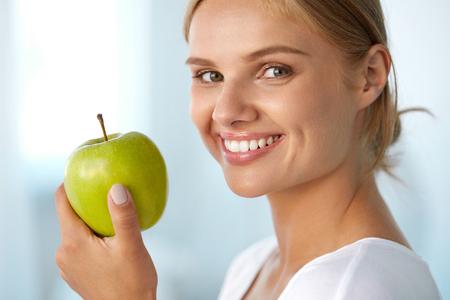 アップルとの女性。幸せ笑顔美少女白のポートレート、クローズ アップの笑顔、自然有機青リンゴを保持して健康な歯。歯の健康は、健康的な食事