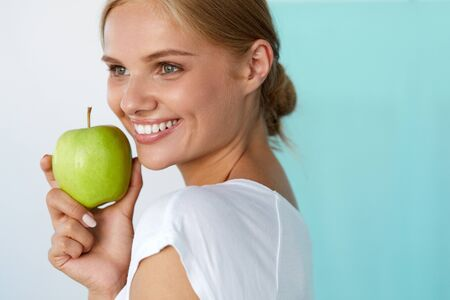 Healthy Diet Food. Closeup Portrait Of Beautiful Happy Smiling Young Woman With Perfect Smile, White Teeth And Fresh Face Holding Organic Green Apple. Dental Health Concept. High Resolution Image