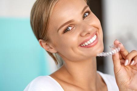 Dientes blancos. Retrato de detalle de hermosa mujer feliz con el blanco perfecto Sonrisa con dientes que blanquea la bandeja. Sonriente, sosteniendo Médico aparatos invisibles. Concepto de la salud dental. Imagen de alta resolución