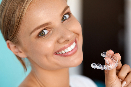 White Teeth. Closeup Portrait Of Beautiful Happy Woman With Perfect White Smile Using Teeth Whitening Tray. Smiling Girl Holding Medical Invisible Braces. Dental Health Concept. High Resolution Image
