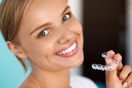 Dientes blancos. Retrato de detalle de hermosa mujer feliz con el blanco perfecto Sonrisa con dientes que blanquea la bandeja. Sonriente, sosteniendo Médico aparatos invisibles. Concepto de la salud dental. Imagen de alta resolución Foto de archivo