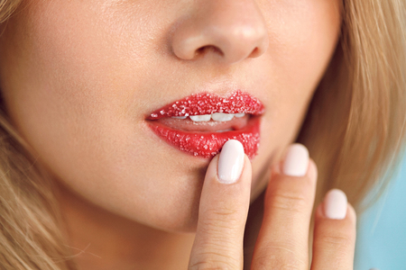 Lip Skin Care. Closeup Of Beautiful Womans Mouth With Cosmetic Sugar Lip Scrub On. Girl Touching, Exfoliating Her Plump Full Lips Using Scrub To Get Soft Lips. Beauty Concept. High Resolution Image Imagens