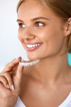 a tooth are beautiful: Teeth Whitening. Beautiful Smiling Woman With White Smile, Straight Teeth Using Teeth Whitening Tray. Girl Holding Invisible Braces, Teeth Trainer. Dental Treatment Concept. High Resolution Image Stock Photo