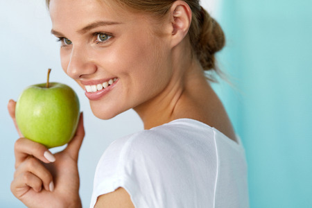 woman diet: Dental Health. Closeup Portrait Of Beautiful Happy Smiling Woman With Perfect Smile, Healthy White Teeth And Fresh Face Holding Green Apple. Healthy Eating, Diet Food Concepts. High Resolution Image