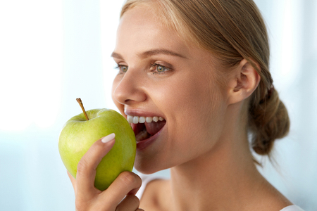 Woman Eating Apple. Closeup Portrait Of Beautiful Happy Woman With Perfect Smile And Healthy White Teeth Biting Organic Green Apple. Dental Health, Diet Food, Nutrition Concepts. High Resolution Image