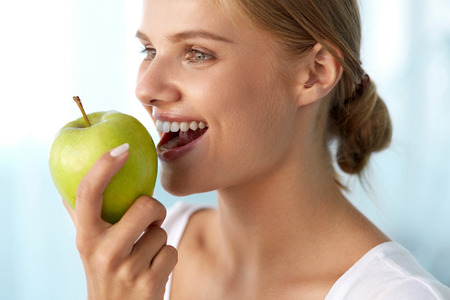 nutrition health: Woman Eating Apple. Closeup Portrait Of Beautiful Happy Woman With Perfect Smile And Healthy White Teeth Biting Organic Green Apple. Dental Health, Diet Food, Nutrition Concepts. High Resolution Image