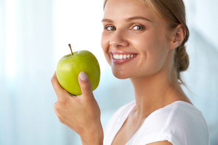 beautiful teeth: Woman With Apple. Closeup Portrait Of Beautiful Happy Smiling Girl With White Smile, Healthy Teeth Holding Natural Organic Green Apple. Dental Health, Healthy Eating Concepts. High Resolution Image Stock Photo