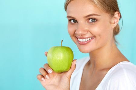 manzana verde: Mujer con la manzana. Retrato de detalle de hermosa muchacha sonriente feliz con la sonrisa blanca, una dentadura sana celebración Natural Organic Green Apple. Salud dental, Conceptos Comida sana. Imagen de alta resolución