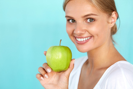 manzana verde: Woman With Apple. Closeup Portrait Of Beautiful Happy Smiling Girl With White Smile, Healthy Teeth Holding Natural Organic Green Apple. Dental Health, Healthy Eating Concepts. High Resolution Image Foto de archivo