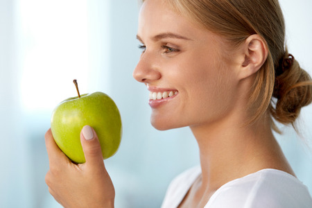 nutrition health: Healthy Nutrition. Closeup Portrait Of Beautiful Smiling Woman With Perfect Smile, White Teeth And Fresh Face Eating Organic Green Apple. Dental Health, Diet Food Concepts. High Resolution Image Stock Photo
