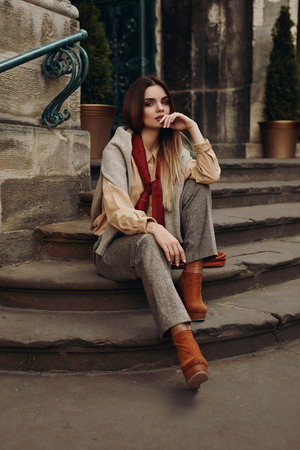 girl shoes: Fashion Model In Street. Beautiful Sexy Woman In Stylish Fashionable Fall Clothes: Shirt, Scarf, Pants, Sweater, Shoes Sitting On Stairs In Spring. Girl In High Fashion Autumn Clothing Posing Outdoors