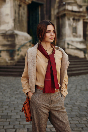 sexy sweater: Fashion Clothes. Beautiful Sexy Woman Wearing High Fashionable Spring, Fall Clothing ( Shirt, Scarf, Pants, Sweater, Leather Bag ) Outdoors. Female Model In Trendy Outfit Posing In The Street