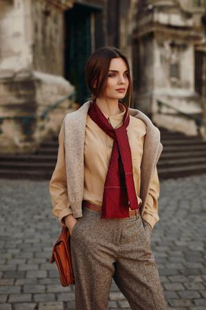 moda ropa: Ropa de moda. Mujer atractiva que desgasta la alta moda de primavera, otoño de ropa (camisa, pañuelo, pantalones, suéter, bolso de cuero) al aire libre. Modelo femenino en el moderno traje Presenta En La Calle