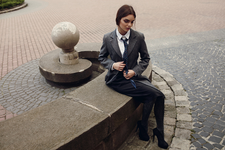 clothing model: Fashion Model In Fashionable Clothing Sitting On The Street. Beautiful Woman In Stylish Fall Clothes Posing Outdoors. Hipster Student Girl In Elegant Coat, Shirt, Skirt, Tie, Tights, High Heels Shoes Stock Photo