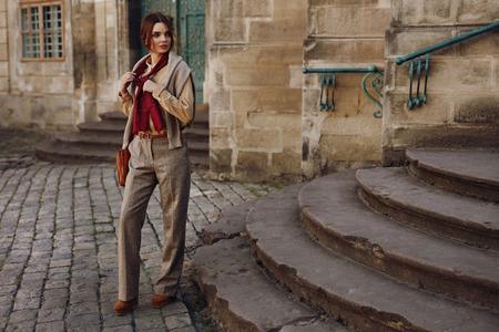 Caída de la mujer. Hermosa chica sexy en ropa de moda con estilo, camisa, bufanda, pantalones, suéter, bolsa, zapatos de pie al aire libre. Modelo de larga duración Mujer en la Alta Costura Ropa presenta en las escaleras