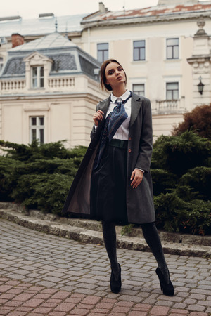 Fashion Model In Fashionable Clothing Walking On The Street. Beautiful Woman In Stylish Fall Clothes Posing Outdoors. Hipster Student Girl In Elegant Coat, Shirt, Skirt, Tie, Tights, High Heels Shoes
