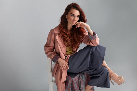 Fashion Model Style. Fashionable Woman In Stylish Clothes Posing On Grey Background In Studio. Beautiful Sexy Girl Wearing Pink Coat, Purple Trousers, Beige Shoes Sitting On Chair. High Resolution Stockfoto