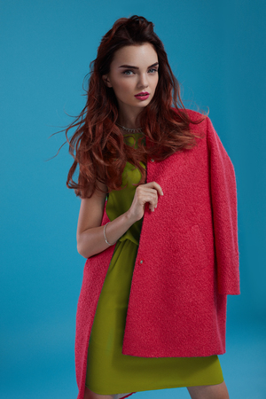 green clothes: Woman Style. Fashion Model Girl In Stylish Fashionable Clothes Standing On Blue Background. Portrait Of Beautiful Sexy Female Wearing Trendy Glamour Clothing, Green Dress And Red Coat. High Resolution