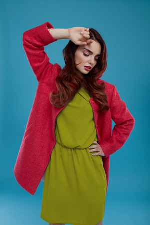green clothes: Fashion Model Girl In High Fashionable Clothing Posing On Blue Background. Beautiful Sexy Woman With Perfect Makeup And Elegant Hairstyle Wearing Trendy Clothes, Green Dress, Stylish Dark Pink Coat Stock Photo