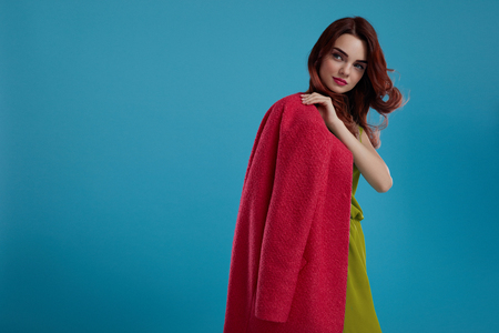 green clothes: Fashion Style. Beautiful Sexy Woman Model In Fashionable Clothes Standing On Blue Background. Portrait Of Glamour Girl Wearing Trendy Stylish Clothing, Green Dress, Crimson Red Coat. High Resolution Stock Photo