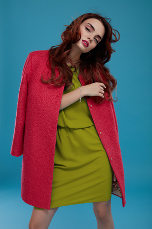 green clothes: Beautiful Woman In Fashion Clothes. Sexy Model Girl In Elegant Fashionable Glamour Clothing Posing On Blue Background. Stylish Female Wearing Trendy Green Dress, Pink Winter Jacket. High Resolution Stock Photo