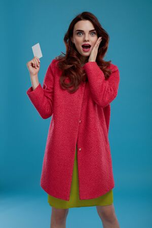 Fashion Model Girl In Stylish Clothes Looking Excited, Shocked And Surprised On Blue Background. Happy Beautiful Sexy Woman In Fashionable Clothing Holding Empty Copy Space Gift Card.  High Resolution Stock Photo