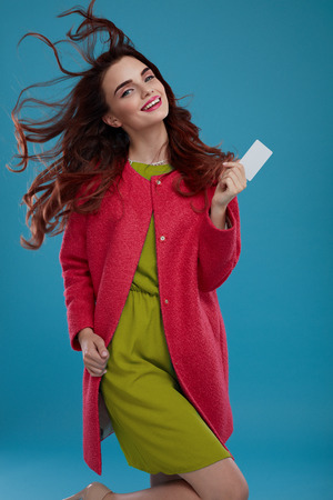 green clothes: Fashion Model Girl In Stylish Clothes On Blue Background. Portrait Of Happy Beautiful Sexy Woman In Fashionable Clothing, Green Dress, Red Coat Holding Empty Copy Space Card In Hand. High Resolution