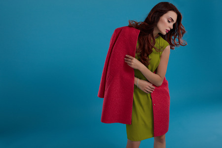 green clothes: Beautiful Fashion Woman Model In Fashionable Clothes Standing On Blue Background. Portrait Of Sexy Glamour Girl In Trendy Stylish Clothing, Green Dress, Red Coat Posing In Studio. High Resolution Stock Photo