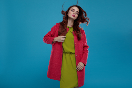 spring green: Fashion Model Girl In High Fashionable Clothing Posing On Blue Background. Beautiful Sexy Woman With Perfect Makeup And Elegant Hairstyle Wearing Trendy Clothes, Green Dress, Stylish Dark Pink Coat Stock Photo