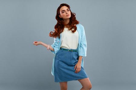 Fashion Girl Model En vêtements à la mode sur fond gris. Belle femme sexy Porter élégant habillement, chemise blanche, Jeans Jupe, Light Blue Coat Veste posant en studio. Haute résolution