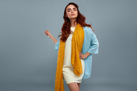 Woman Style And Fashion. Portrait Of Beautiful Sexy Model Girl In Stylish Fashionable Clothes, White Dress, Light Blue Coat Jacket, Yellow Scarf  Posing On Grey Background In Studio. High Resolution Stock Photo