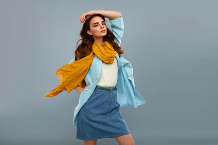 fashion: Fashion Model Girl In Fashionable Clothes On Grey Background. Beautiful Sexy Woman Wearing Stylish Clothing, White Shirt, Jeans Skirt, Light Blue Coat Jacket, Yellow Scarf In Studio. High Resolution