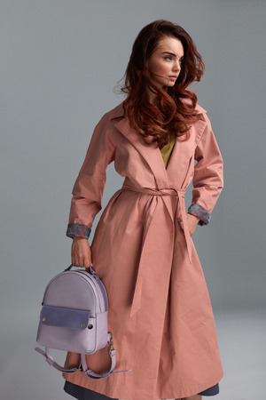 light hair: Woman Style And Fashion Clothes. Female Model Wearing Stylish Fashionable Clothing, Light Pink Coat, Purple Backpack Bag On Grey Background. Beautiful Girl Posing In Studio Portrait. High Resolution Stock Photo