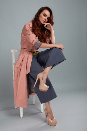 Fashion Model Style. Fashionable Woman In Stylish Clothes Posing On Grey Background In Studio. Beautiful Sexy Girl Wearing Pink Coat, Purple Trousers, Beige Shoes Sitting On Chair. High Resolution Stock Photo