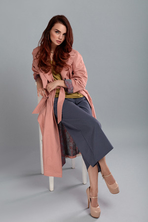 purple shoes: Fashion Model Style. Fashionable Woman In Stylish Clothes Posing On Grey Background In Studio. Beautiful Sexy Girl Wearing Pink Coat, Purple Trousers, Beige Shoes Sitting On Chair. High Resolution Stock Photo