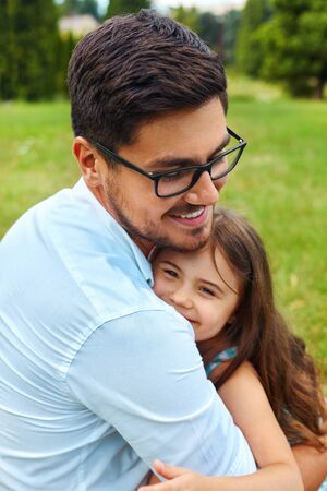 family relationships: Father And Daughter Hugging In Park. Happy Smiling Young Parent Embraces His Kid Outdoors. Dad And Child Spending Leisure Time Together In Nature. Family Relationships And Love Concept