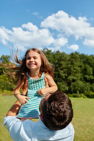 family relationships: Happy Father And Child Having Fun Playing Outdoors. Smiling Young Dad And Daughter Spending Time Together In Nature. Parent And His Kid Relaxing In Park. Family Time, Relationships Concept Stock Photo
