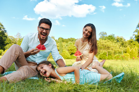 eating fruits: Family In Park. Happy Beautiful Young Parents And Smiling Child Having Fun On Picnic In Park, Kid Eating Fruits. People Relaxing And Spending Time Together Outdoors, In Nature. Relationship Concept
