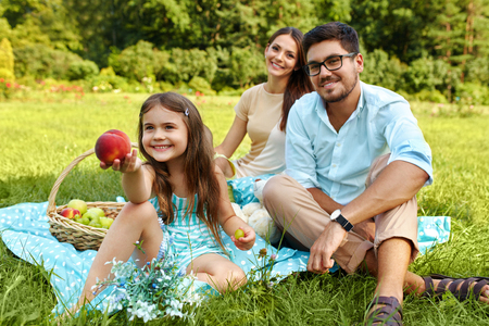 family in park: Family On Picnic. Happy Beautiful Young Family Spending Leisure Time Together In Park, Kids Eating Fruits And Having Fun In Nature. Smiling Parents And Children Relaxing Outdoors. Relationship Concept