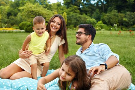 weekend activities: Happy Young Family On Picnic In Park. Smiling Parents And Children Having Fun, Playing, Spending Leisure Time Together In Nature. Kids And Adults Relaxing Outdoors On Weekend. Relationships Concept